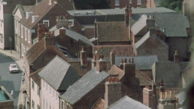 montage rooftops of rowhouses and buildings are closely spaced in the city / london, england, united kingdom - villetta a schiera casa video stock e b–roll