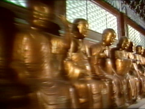 statues room filled w/ gold buddha statues dolly past seated statues - buddha stock videos & royalty-free footage