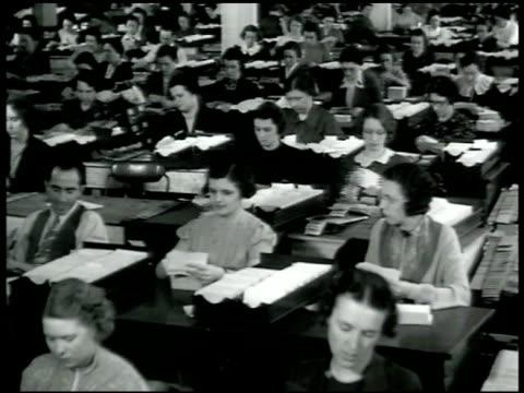 vidéos et rushes de room full of clerks sitting at desks filing index cards ms women clerks seated at desks going through index cards - 1942