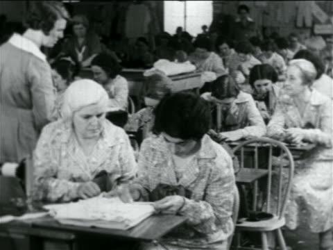b/w 1934 room full of women sewing in wpa garment factory / documentary - 雇用促進局点の映像素材/bロール