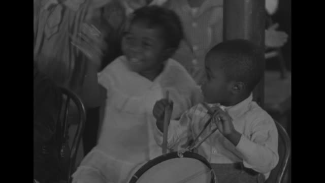 room full of young african-american children sits in classroom, some with instruments; boy walks up to chair, climbs to stand on it, facing the... - drum percussion instrument stock videos & royalty-free footage