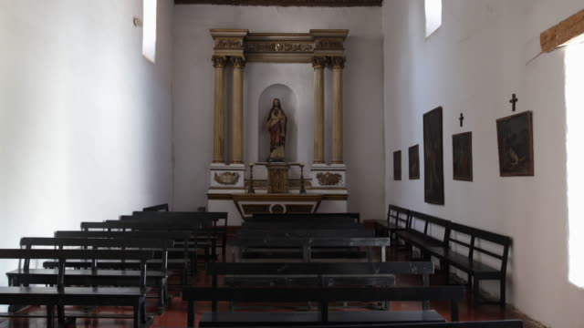 room in a church with benches and the statue of jesus christ under an arch which has two golden stands on each sides and candles the roof is made of... - jesuit stock videos and b-roll footage