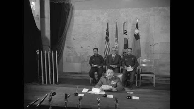 room with leaders of belligerent parties of korean war seated in front of standing flags of us, un, south korea, and republic of china army, map... - 将校点の映像素材/bロール