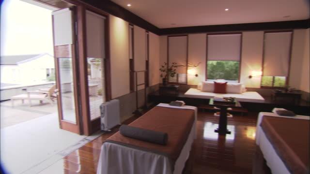 vídeos de stock e filmes b-roll de a  room with massage tables opens onto a patio in shanghai, china. - mesa de massagem