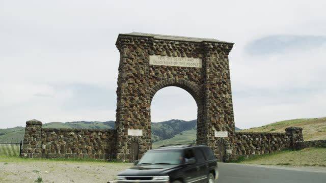 vídeos de stock e filmes b-roll de roosevelt arch, entrance to the north gate of yellow park, yellowstone np, united states - arco caraterística arquitetural