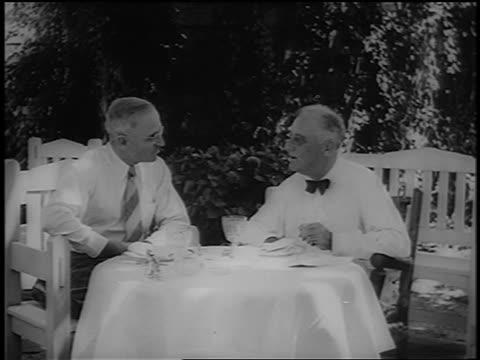 roosevelt + harry s. truman sit + talk at table on patio outdoors / newsreel - 副代表点の映像素材/bロール
