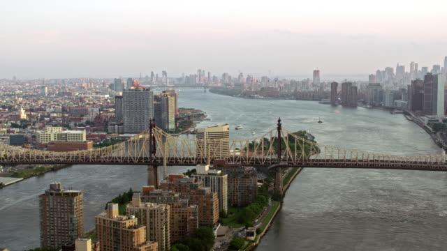 aerial roosevelt island with the queensborough bridge overlooking the new york city - queensboro bridge stock videos & royalty-free footage