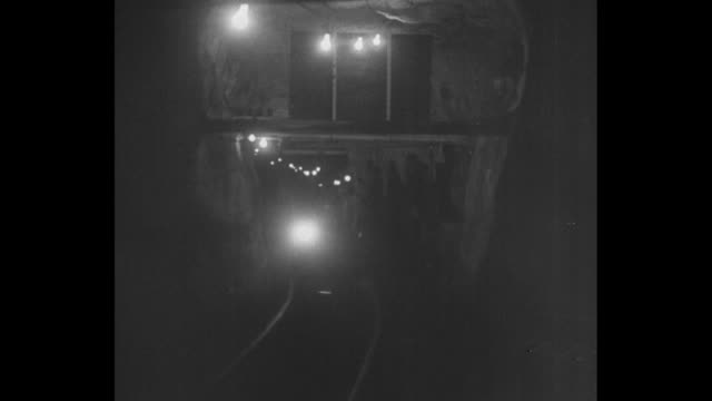 Roosevelt seated in a coal worker's transport car with American flag behind her / headlamps of worker's helmets roll in underground darkness / she's...