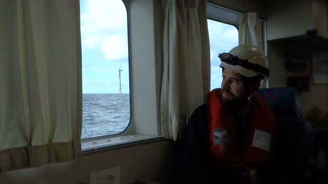rope access technician sitting in the cabin of passenger ship and looking from window on offshore find farm. blue wavy sea and moody, dramatic sky. germany, borkum riffgrund wind farm. - sailor stock videos & royalty-free footage