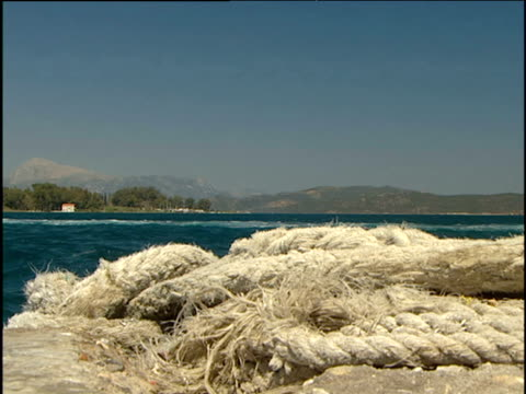 rope gently rocks waves lap in foreground while sea leads to mountains and shoreline of the saronic islands in background. - ausgefranst stock-videos und b-roll-filmmaterial