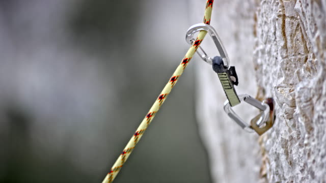 slo mo rope gliding through a quickdraw in the rock wall - climbing equipment stock videos & royalty-free footage