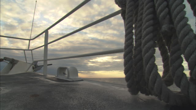 rope hangs on the railing of a ship as it sails the ocean. - ship's bow stock videos & royalty-free footage