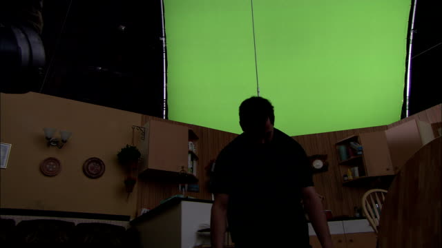 a rope hoists a man upwards in front of a green screen as utensils and paper blow around a kitchen in the wind. - hoisting stock videos & royalty-free footage