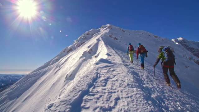 rope team of mountaineers walking up the mountain - wide stock-videos und b-roll-filmmaterial