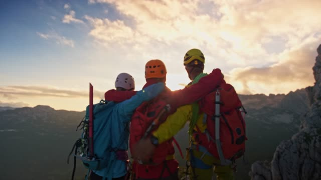 rope team of three mountaineers reaching the mountain top at sunset - adventure stock videos & royalty-free footage
