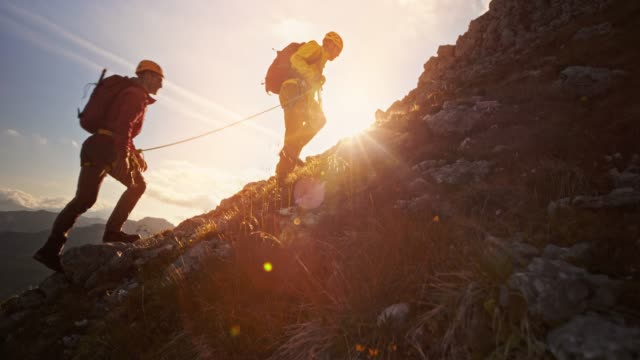 rope team of two mountaineers climbing the mountain in setting sun - climbing rope stock videos & royalty-free footage