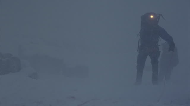stockvideo's en b-roll-footage met roped mountain climbers struggle through a snowstorm when a climber falls and tumbles past the camera. - sneeuwstorm