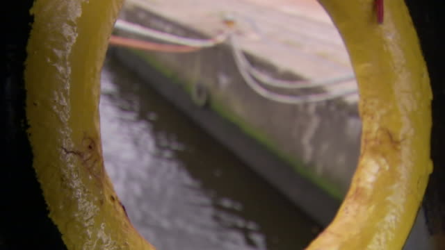 vidéos et rushes de ropes extend from a pier towards a ship's porthole. - hublot