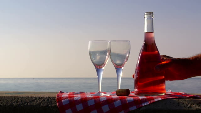 Rosé wine poured into glasses at the beach