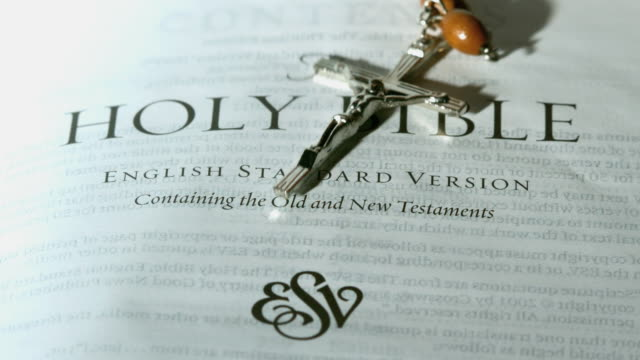 Rosary beads falling onto first page of the holy bible