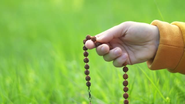 rosary beads. harmony. close-up of a hand holding a rosary while saying a prayer while being in the nature. religion - bead stock videos & royalty-free footage