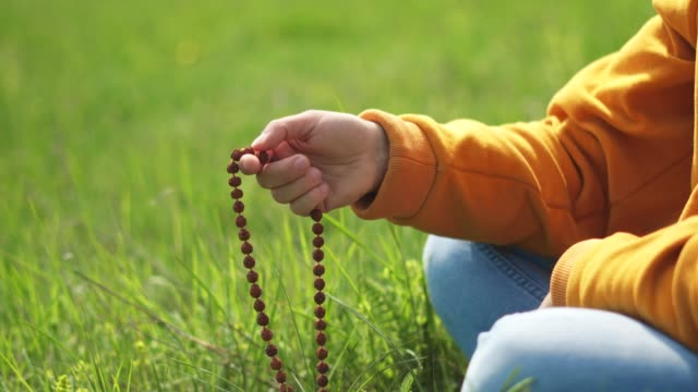 rosary beads. harmony. close-up of a hand holding a rosary while saying a prayer while being in the nature. religion - worry beads stock videos & royalty-free footage