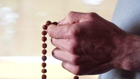vídeos de stock, filmes e b-roll de grânulos do rosário. harmonia. close-up da mão de um homem que prende um rosário ao dizer uma oração. religião - conta artigo de armarinho