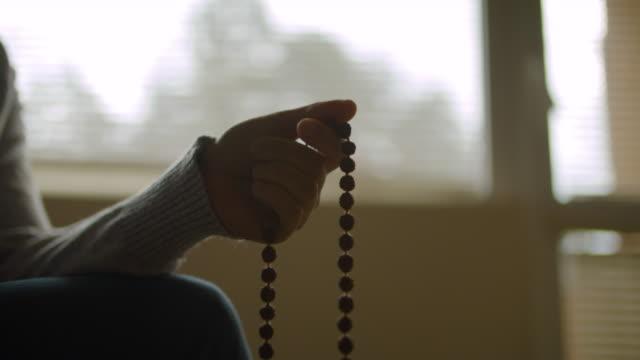 vídeos de stock, filmes e b-roll de contas de rosário. harmonia. close-up de uma pessoa segurando um rosário enquanto reza. religião - equilíbrio