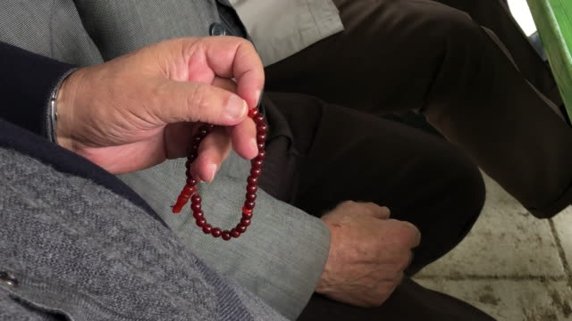 rosary beads in senior adult man hand - rosary beads stock videos & royalty-free footage