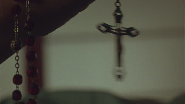 vídeos de stock, filmes e b-roll de a rosary cross dangles and swings back and forth. - religião
