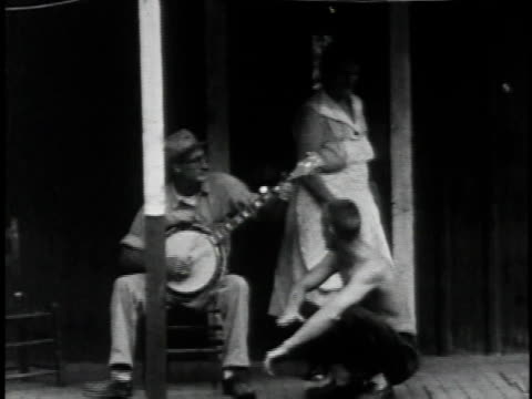 stockvideo's en b-roll-footage met 1962 montage roscoe holcomb playing banjo and singing to man and woman on porch and over shots of mountains / kentucky, united states - stem thema