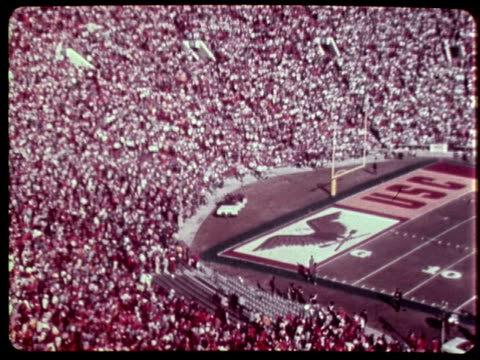 rose bowl between usc trojans and ohio state buckeyes / cheering crowd on their feet in spectator stands at rose bowl stadium / young women riding in... - カリフォルニア州 パサデナ点の映像素材/bロール