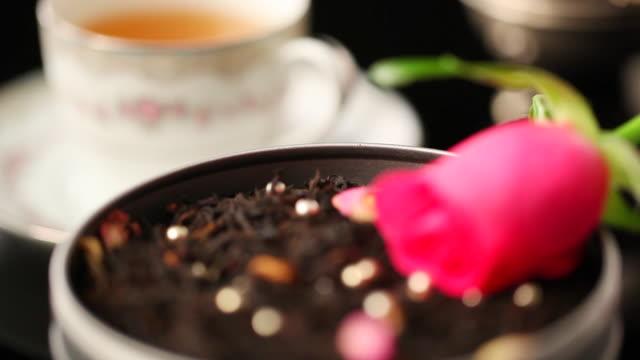 ecu r/f rose on black tea leaves and cup of tea / seoul, south korea - dried tea leaves stock videos & royalty-free footage