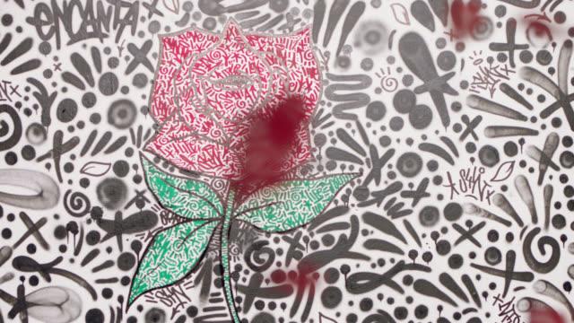 rose petals fall as camera pushes in on red rose graffiti in white art studio. - 美術工芸品点の映像素材/bロール