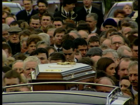 Rosemary Nelson funeral ITN NORTHERN IRELAND County Armagh Lurgan Coffin of Rosemary Nelson carried along from house GV crowd of mourners towards...