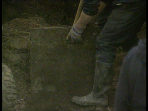 stockvideo's en b-roll-footage met prosecution completes its case; march 1994 gloucester: cromwell st: no. 25: tms paving slab lifted in garden tms police officer in trench examining... - artikel