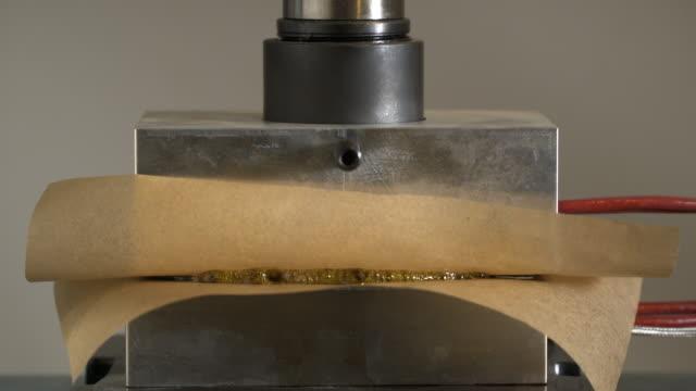 rosin press melting marijuana plant onto parchment. - parchment stock videos & royalty-free footage