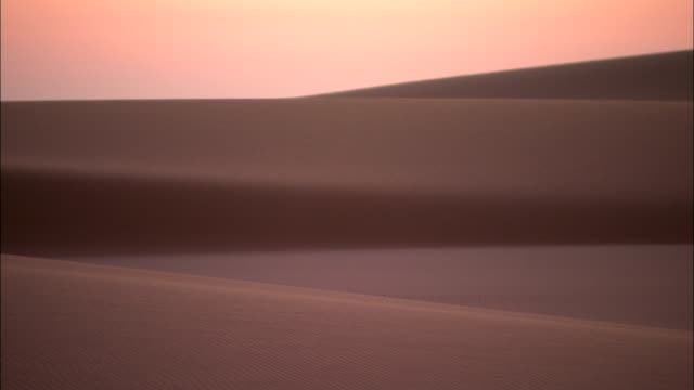 vídeos de stock e filmes b-roll de a rosy sky glows above sand dunes. - horizon