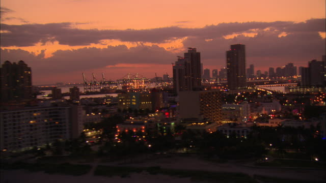 a rosy sky glows above south beach and downtown miami at sunset. - south beach stock videos & royalty-free footage