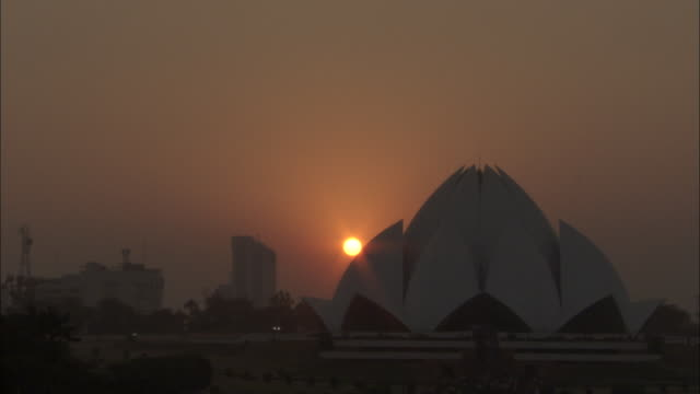 a rosy sun glows behind the bahai house of worship in delhi, india. - delhi stock videos & royalty-free footage
