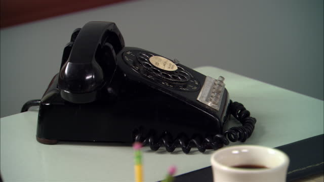 cu rotary phone sitting on desk next to coffee cup/ new york city - disco combinatore video stock e b–roll