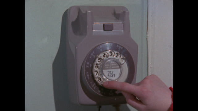 vidéos et rushes de rotary telephone on wall, hand picks up receiver and dials 999. - téléphone à fil