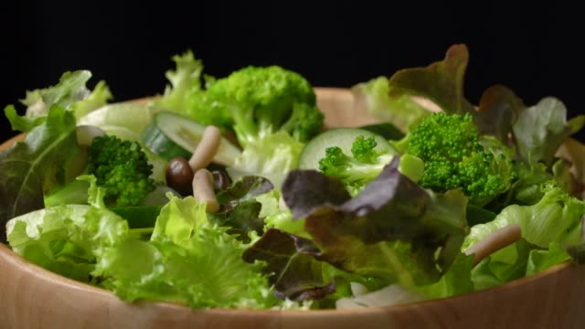 rotate of green salad bowl on black background - salad bowl stock videos & royalty-free footage