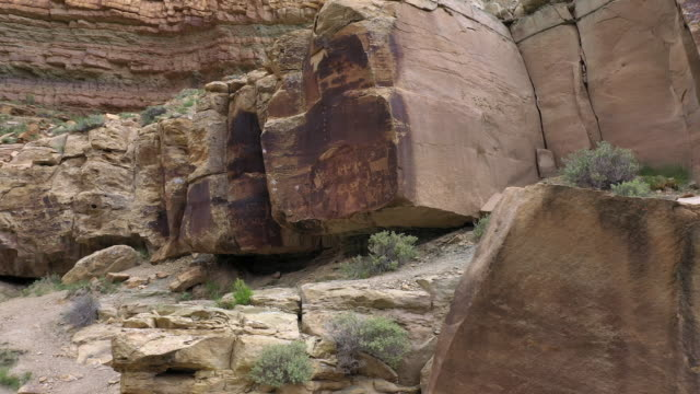 rotating aerial view of petroglyphs on rock in utah - anasazi stock videos & royalty-free footage