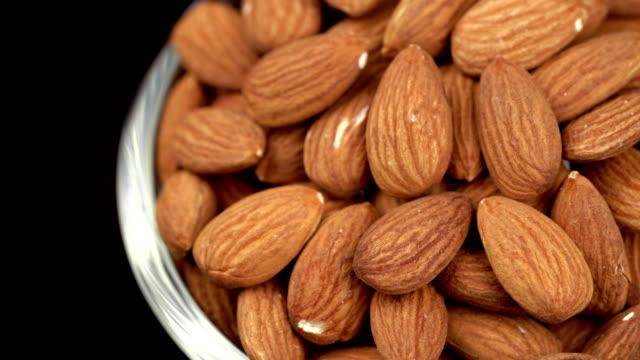 4k rotating almond on black background - nutshell stock videos & royalty-free footage