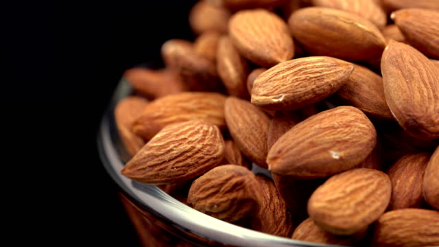 4k rotating almond on black background - bowl stock videos & royalty-free footage