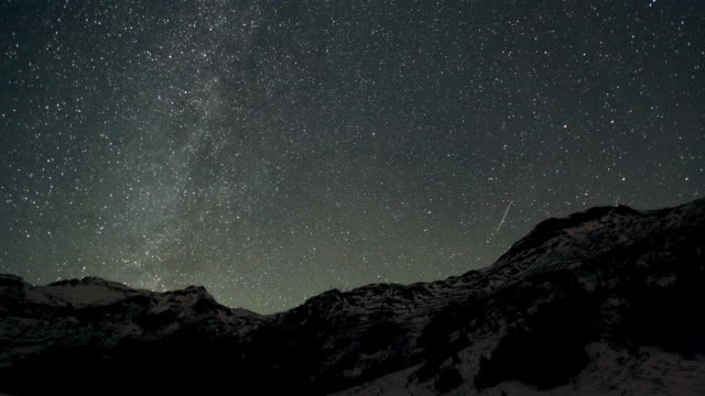 Rotating and shooting stars over snowy mountainous pastoral scene
