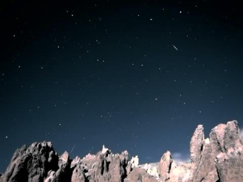 vídeos de stock, filmes e b-roll de rotating and shooting stars to dawn over jagged mountain timelapse - chuva de meteoros