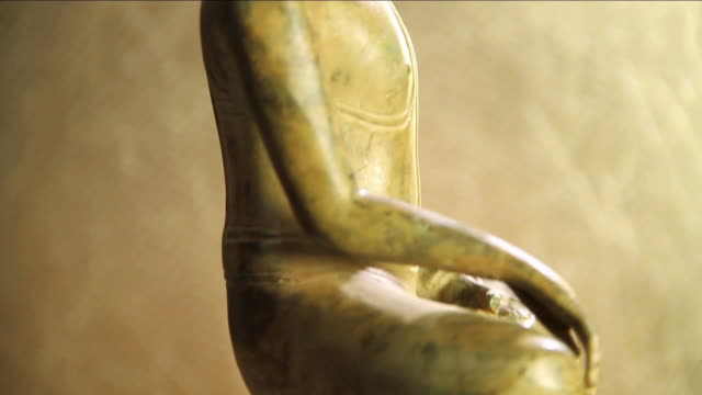 vídeos de stock e filmes b-roll de ms tu slo mo rotating buddha statue carved in stone against of gold background / miami, florida, united states - buda