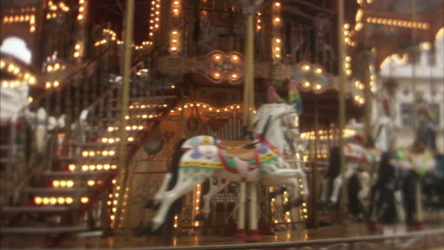 cu rotating carousel, paris, france - carousel horse stock videos and b-roll footage